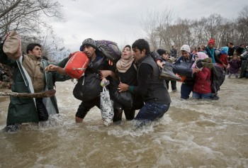 A woman is supported by two men while crossing a river as migrants attempt to reach Macedonia on a route that would bypass the border fence, Monday, March 14, 2016. Hundreds of migrants and refugees walked out of an overcrowded camp on the Greek-Macedonian border Monday, determined to use a dangerous crossing to head north.(AP Photo/Vadim Ghirda)