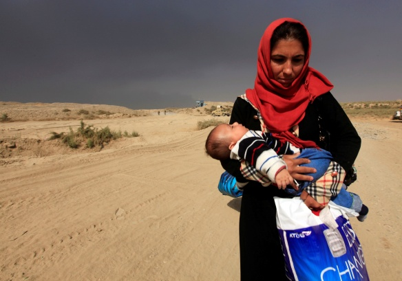 A displaced woman who is fleeing from clashes holds her baby in Qayyarah